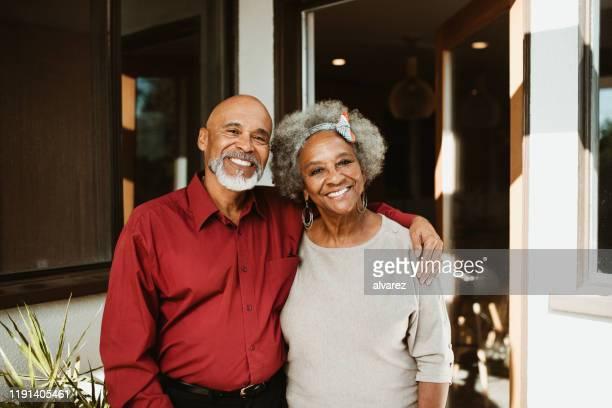 pensionato sorridente in piedi con il braccio intorno alla moglie - coppia anziana foto e immagini stock