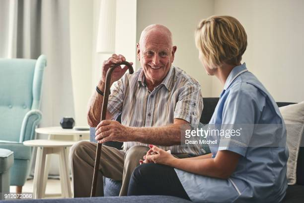 smiling retired man with female home carer - visit stock pictures, royalty-free photos & images
