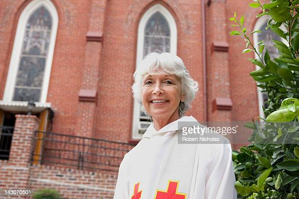 smiling reverend standing outside church - pastor stock pictures, royalty-free photos & images