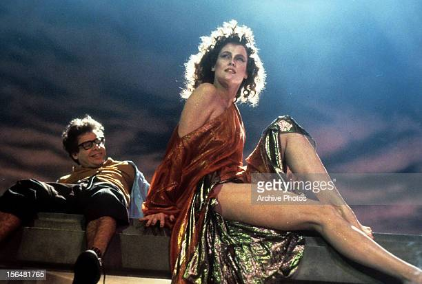 A smiling Rick Moranis looking up at Sigourney Weaver in a scene from the film 'Ghostbusters' 1984