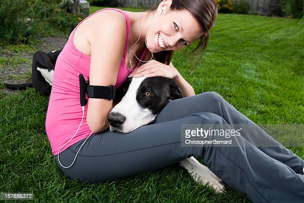 Smiling runner hugging her dog
