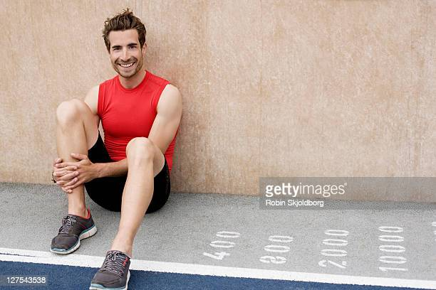 Smiling runner sitting against wall