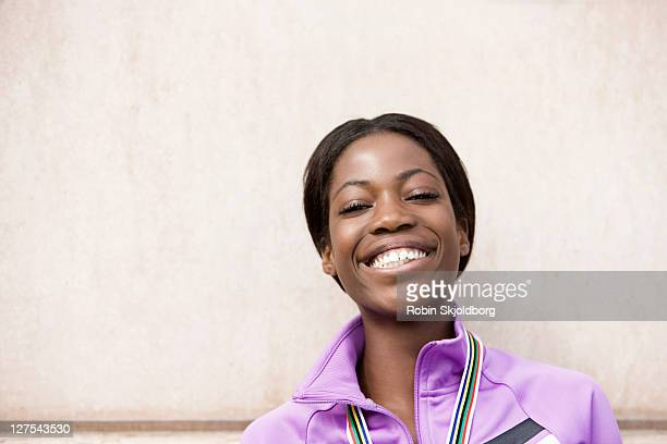 smiling runner wearing medal - medalist stock photos and pictures
