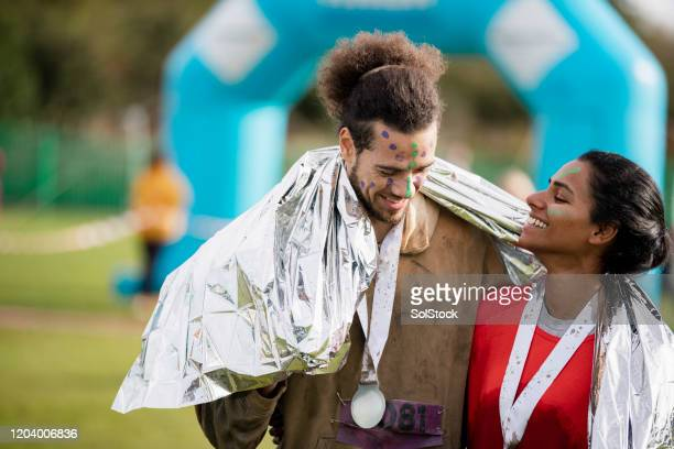 smiling runners sharing foil blanket after stampede race - medallist stock pictures, royalty-free photos & images