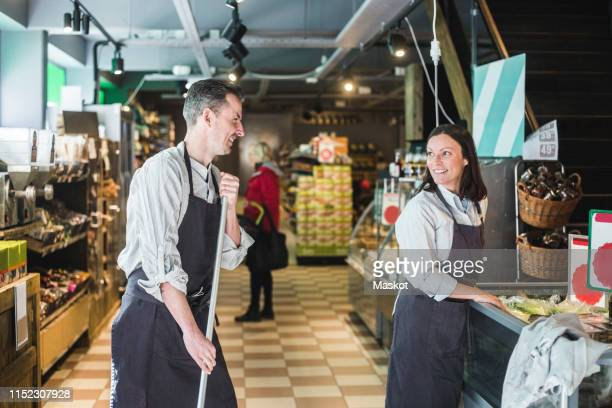 smiling sales clerk holding broom while looking at saleswoman in supermarket - sweeping stock pictures, royalty-free photos & images