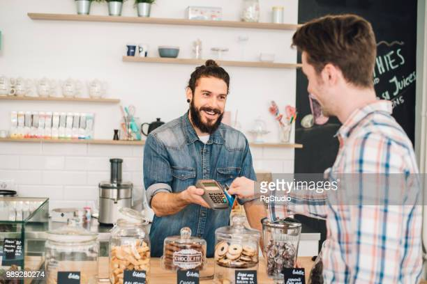 smiling sales man assisting customer in credit card purchase - credit card reader stock pictures, royalty-free photos & images