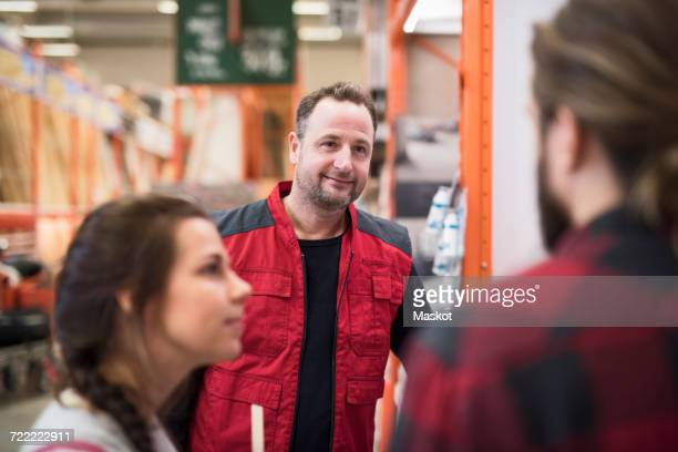 smiling salesman looking at couple in hardware store - bricolage photos et images de collection