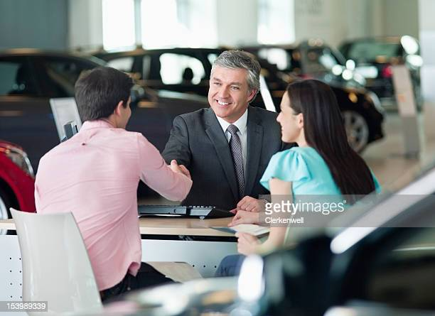 Smiling salesman shaking hands with couple at desk in car dealership showroom
