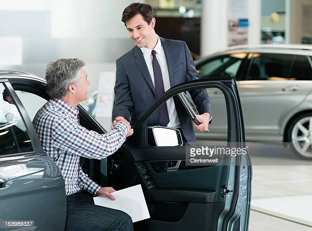 smiling salesman shaking manõs hand in car dealership showroom - car salesperson stock pictures, royalty-free photos & images