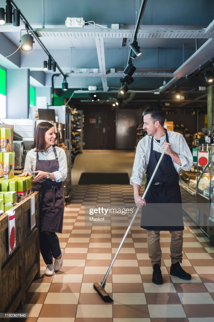 Smiling Salesman Sweeping Floor While Looking At Colleague In