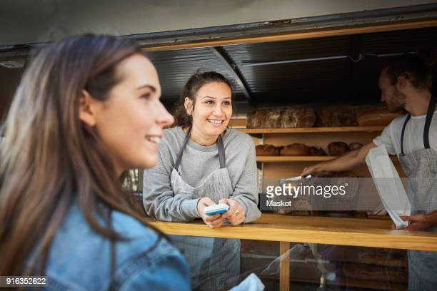 Smiling saleswoman accepting payment from customer while colleague packing bread at concession stand