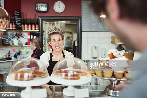 Smiling saleswoman attending customer in supermarket