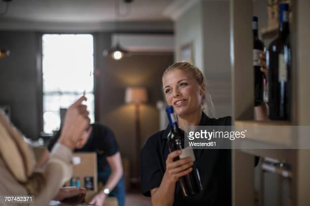 Smiling saleswoman packing wine bottles on shelf in wine shop
