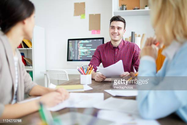 Smiling satisfied young man with papers meeting with colleagues in modern office: he talking to staff