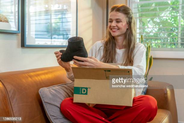 smiling satisfied young woman customer sit on sofa unpack package open parcel, happy girl consumer holding cardboard box receive good online shop purchase at home, post mail shipping delivery concept - open source stock-fotos und bilder