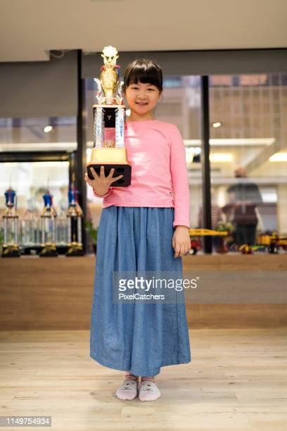 menina de sorriso da escola que está na sala de aula que prende o grande troféu que ganhou - trophy - fotografias e filmes do acervo