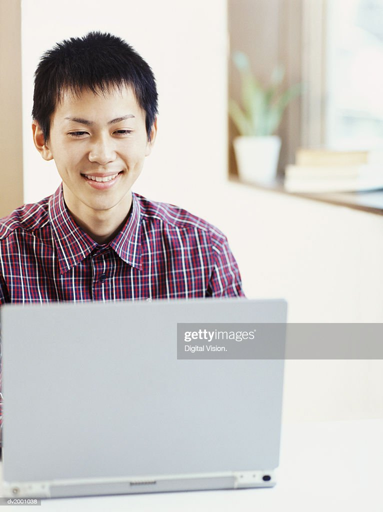 Smiling Schoolboy Doing His Homework on a Laptop : Stock Photo