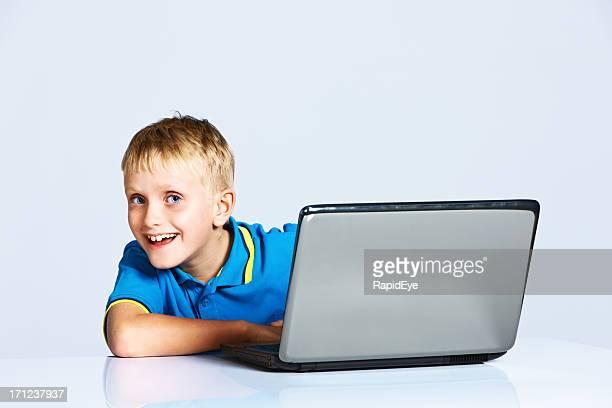 Smiling schoolboy peeps round open laptop