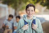 Smiling schoolboy standing with schoolbag in campus