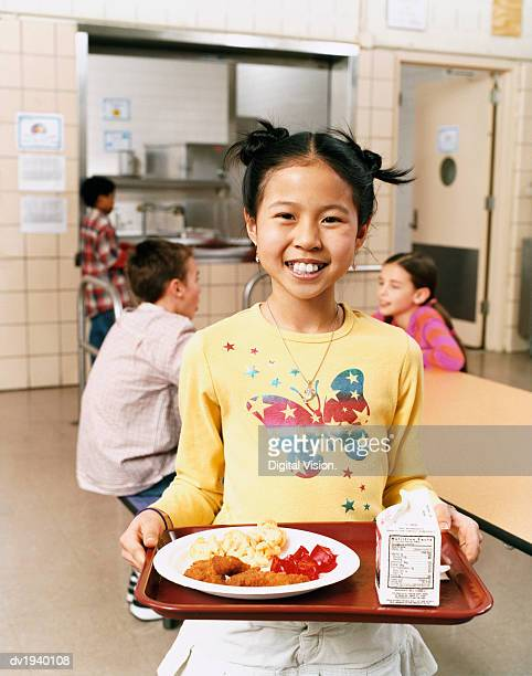smiling schoolgirl carrying a tray with food - milk carton stock photos and pictures