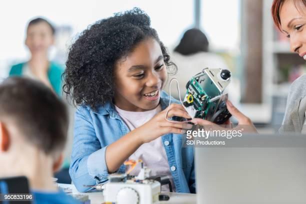 sorrir colegial cria robô na aula de tecnologia - robô - fotografias e filmes do acervo