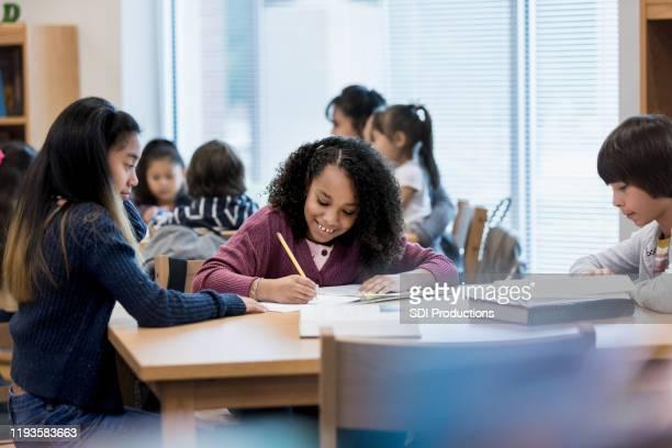 smiling schoolgirl enjoys studying with her friends - aluna da escola secundária imagens e fotografias de stock