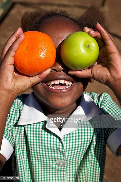 Smiling schoolgirl holds an apple and an orange, KwaZulu Natal Province, South Africa