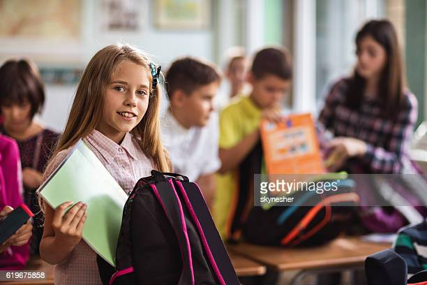 Smiling schoolgirl in the classroom packing her books into backpack.