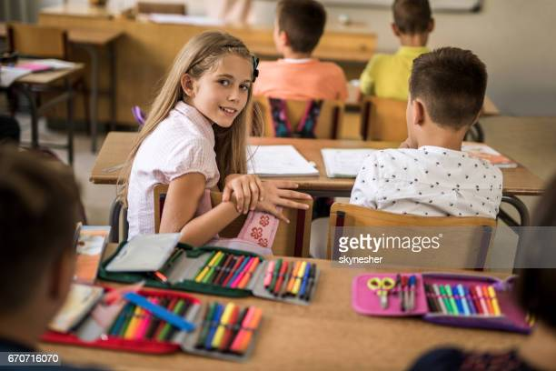 Smiling schoolgirl looking at camera during lecture in the classroom.
