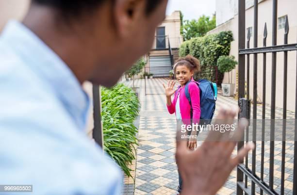 女子高生の学校外の父に手を振って笑顔