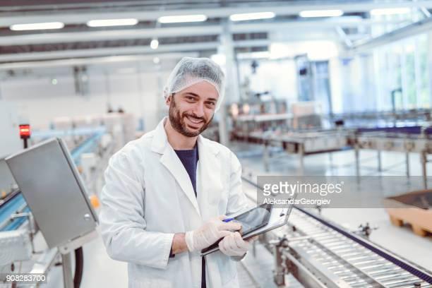 Smiling Scientist Controller Doing Revision in Bottling Plant