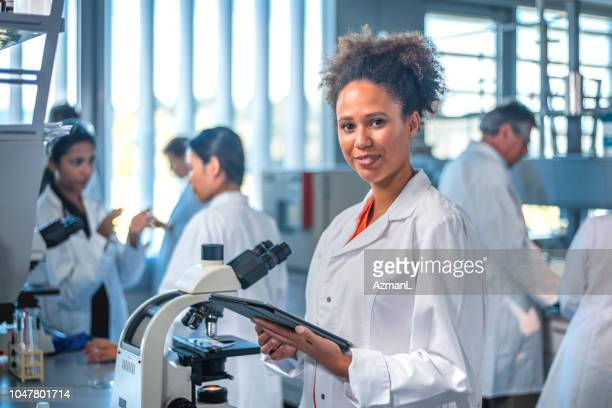 smiling scientist with digital tablet in laboratory - technician stock pictures, royalty-free photos & images
