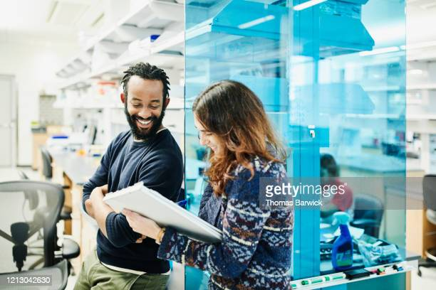 smiling scientists in discussion while filling out paperwork in research lab - scientificsubjects stock pictures, royalty-free photos & images