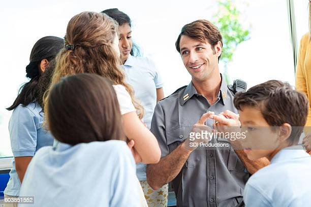 Smiling security guard talks with school children