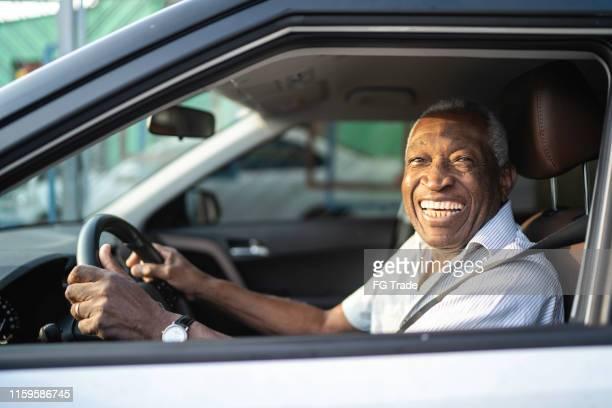homem afro sênior de sorriso que conduz um carro e que olha a câmera - direção - fotografias e filmes do acervo