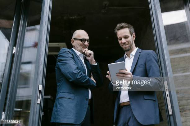smiling senior and mid-adult businessman with tablet having a meeting - successor stock pictures, royalty-free photos & images