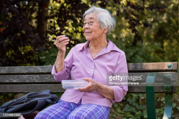 smiling senior asian woman relaxing in park and eating blueberries - reusable stock pictures, royalty-free photos & images
