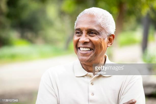 uomo nero senior sorridente all'aperto - uomini anziani foto e immagini stock