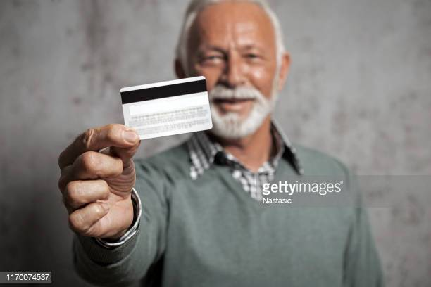 smiling senior businessman holding credit card - greeting card stock pictures, royalty-free photos & images
