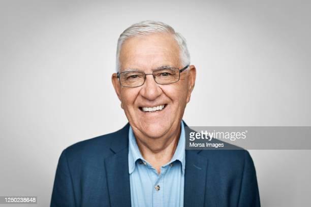 smiling senior businessman on white background - porträt stock-fotos und bilder