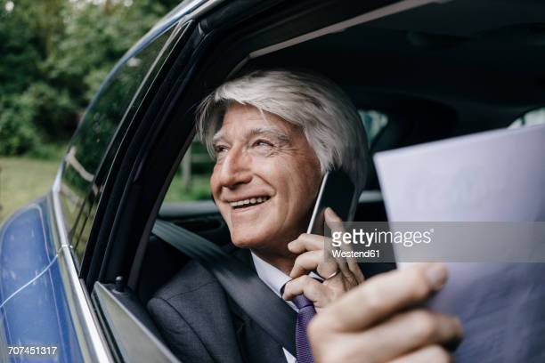 Smiling senior businessman with documents on the phone in a car