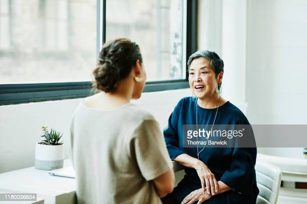 smiling senior businesswoman in discussion with client in office conference room - 話し合い ストックフォトと画像
