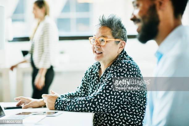 smiling senior businesswoman in discussion with colleague in coworking office - mid section stock pictures, royalty-free photos & images