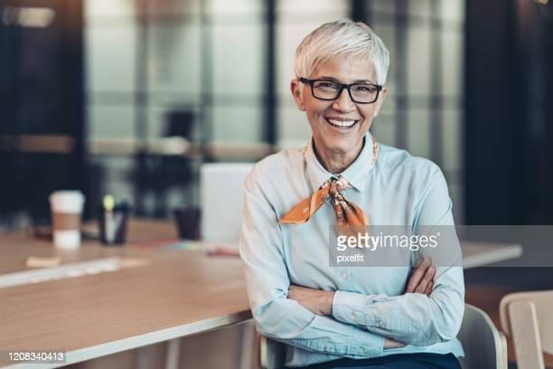 femme d'affaires aînée de sourire dans le bureau - directeur exécutif photos et images de collection