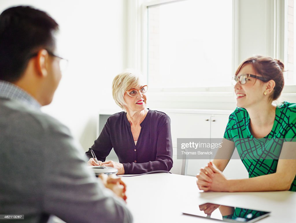 Smiling senior businesswoman leading discussion : Stock Photo