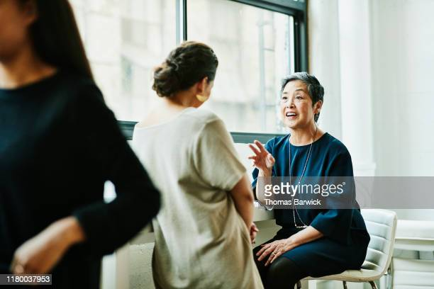 smiling senior businesswoman leading project discussion with colleague in office conference room - femmes d'âge moyen photos et images de collection