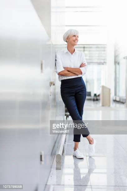 smiling senior businesswoman leaning against a wall - leaning stock pictures, royalty-free photos & images
