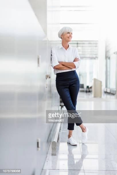 smiling senior businesswoman leaning against a wall - lehnend stock-fotos und bilder
