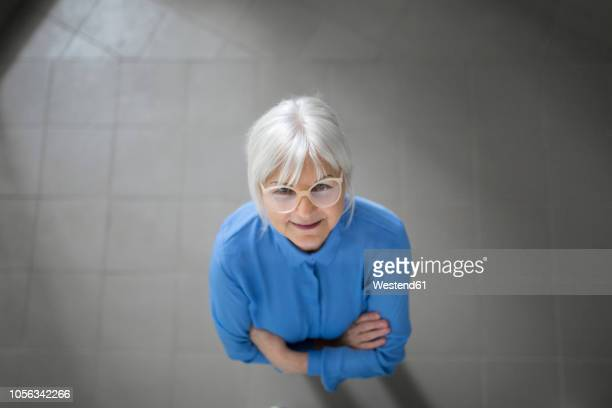 smiling senior businesswoman looking up on office hallway - looking down her blouse stock photos and pictures