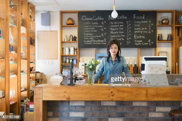 smiling senior cafe owner in coffee shop - カフェ ストックフォトと画像
